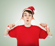 Young man in funny santa hat with pigtails Royalty Free Stock Image