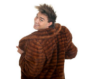 Young man in a fur coat Stock Images