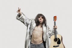 Young man in fur coat holding guitar while gesturing over gray background Royalty Free Stock Photography