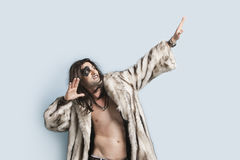 Young man in fur coat looking up with arms raised against light blue background Stock Photography