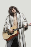 Young man in fur coat playing guitar over gray background Stock Photos