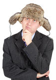 Young man in a fur hat dreams on white background Royalty Free Stock Image
