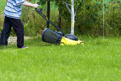 Young man gardener using lawn mower Royalty Free Stock Photography