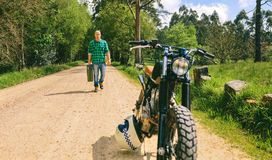 Man with gasoline can walking to custom vintage motorbike. Young man with gasoline can walking to custom vintage motorbike on the side of the road. Selective stock image