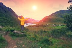 The young man gazing sunset. Panoramic view of the fjord. Twilight time with an amazing orange sky. The young man with hands in the air standing on the stone and stock image