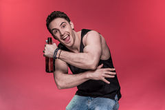 Young man gesturing with beer bottle and smiling at camera Royalty Free Stock Images