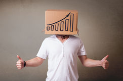 Young man gesturing with a cardboard box on his head with diagra Stock Photo