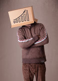 Young man gesturing with a cardboard box on his head with diagra Royalty Free Stock Photography