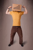 Young man gesturing with a cardboard box on his head with diagra Stock Image