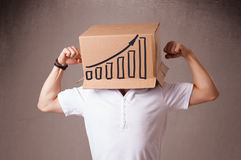 Young man gesturing with a cardboard box on his head with diagra Royalty Free Stock Photo