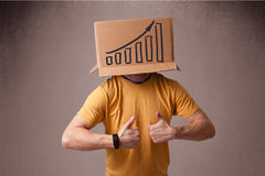 Young man gesturing with a cardboard box on his head with diagra Royalty Free Stock Photos