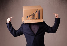 Young man gesturing with a cardboard box on his head with diagra Stock Photography