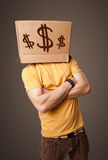 Young man gesturing with a cardboard box on his head with dollar Royalty Free Stock Photo