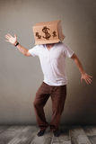 Young man gesturing with a cardboard box on his head with dollar Royalty Free Stock Photography
