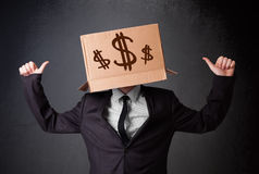 Young man gesturing with a cardboard box on his head with dollar Royalty Free Stock Images