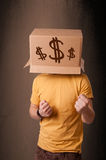 Young man gesturing with a cardboard box on his head with dollar Stock Photos