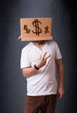 Young man gesturing with a cardboard box on his head with dollar Stock Images