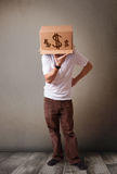 Young man gesturing with a cardboard box on his head with dollar Stock Image