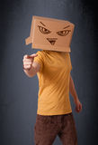 Young man gesturing with a cardboard box on his head with evil f Royalty Free Stock Photography