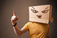 Young man gesturing with a cardboard box on his head with evil f Royalty Free Stock Photos