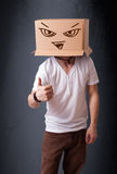 Young man gesturing with a cardboard box on his head with evil f Stock Photography