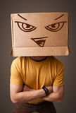 Young man gesturing with a cardboard box on his head with evil f Royalty Free Stock Images