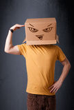 Young man gesturing with a cardboard box on his head with evil f Stock Image