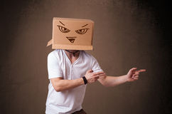Young man gesturing with a cardboard box on his head with evil f Royalty Free Stock Image