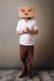 Young man gesturing with a cardboard box on his head with evil f Stock Photo