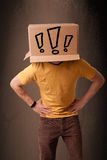 Young man gesturing with a cardboard box on his head with exclam Stock Photos