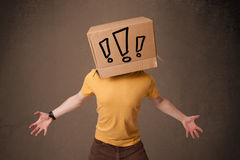 Young man gesturing with a cardboard box on his head with exclam Stock Photography