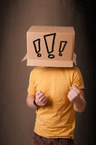 Young man gesturing with a cardboard box on his head with exclam Stock Images