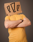 Young man gesturing with a cardboard box on his head with exclam Royalty Free Stock Image