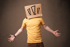 Young man gesturing with a cardboard box on his head with exclam Stock Photo