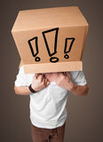Young man gesturing with a cardboard box on his head with exclam Royalty Free Stock Photography