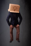 Young man gesturing with a cardboard box on his head with light Stock Photography