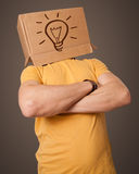 Young man gesturing with a cardboard box on his head with light Royalty Free Stock Photography