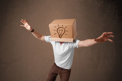 Young man gesturing with a cardboard box on his head with light Royalty Free Stock Photos