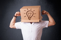 Young man gesturing with a cardboard box on his head with light Stock Image