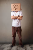 Young man gesturing with a cardboard box on his head with light Royalty Free Stock Photo