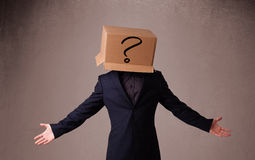 Young man gesturing with a cardboard box on his head with questi Stock Images