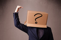 Young man gesturing with a cardboard box on his head with questi Royalty Free Stock Image