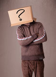 Young man gesturing with a cardboard box on his head with questi Stock Photos