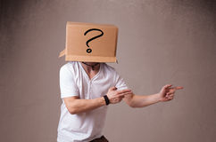 Young man gesturing with a cardboard box on his head with questi Royalty Free Stock Photography