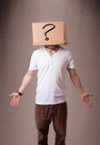 Young man gesturing with a cardboard box on his head with questi Royalty Free Stock Photos