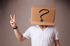 Young man gesturing with a cardboard box on his head with questi Stock Photo
