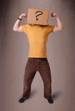 Young man gesturing with a cardboard box on his head with questi Royalty Free Stock Photo