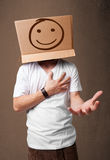 Young man gesturing with a cardboard box on his head with smiley Royalty Free Stock Image