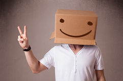 Young man gesturing with a cardboard box on his head with smiley. Young man standing and gesturing with a cardboard box on his head with smiley face Royalty Free Stock Images