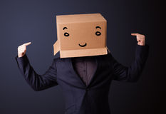 Young man gesturing with a cardboard box on his head with smiley Royalty Free Stock Images
